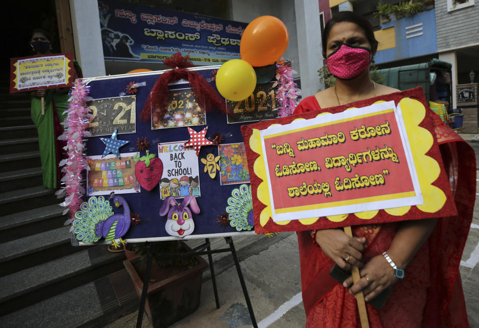 A teacher wearing face mask as a precaution against the coronavirus holds a placard that reads 'let's chase away coronavirus pandemic and get back students to school for education' outside Blossoms High School in Bengaluru, India, Friday, Jan. 1, 2021. The southern state of Karnataka on Friday opened schools for students of grade 10 and 12 after a gap of more than nine months. India has more than 10 million cases of coronavirus, second behind the United States. (AP Photo/Aijaz Rahi)