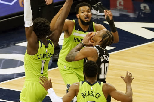 San Antonio Spurs' DeMar DeRozan, center, looks at the basket as Minnesota Timberwolves' Karl-Anthony Towns looms over him in the second half of an NBA basketball game Saturday, Jan. 9, 2021, in Minneapolis. (AP Photo/Jim Mone)