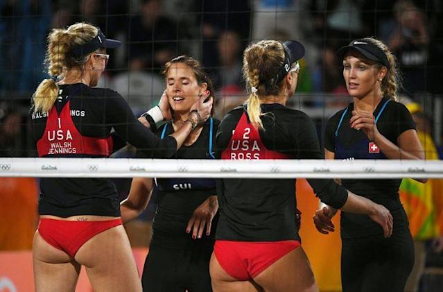 USA's Kerri Walsh Jennings (L) and April Ross hug Switzerland's players after winning the women's beach volleyball qualifying match between the USA and Switzerland. (Getty)