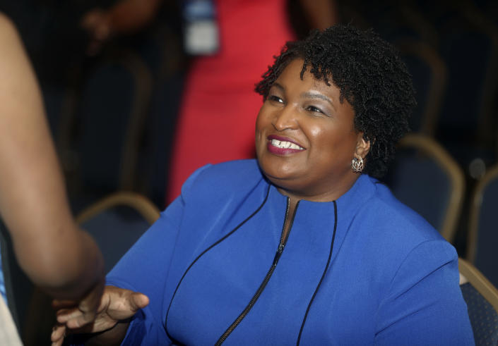FILE- In this Aug. 3, 2018, file photo, Georgia gubernatorial candidate Stacey Abrams is greeted before speaking at the National Association of Black Journalists in Detroit. Abrams is aiming to become the nation's first black female governor. (AP Photo/Carlos Osorio, File)