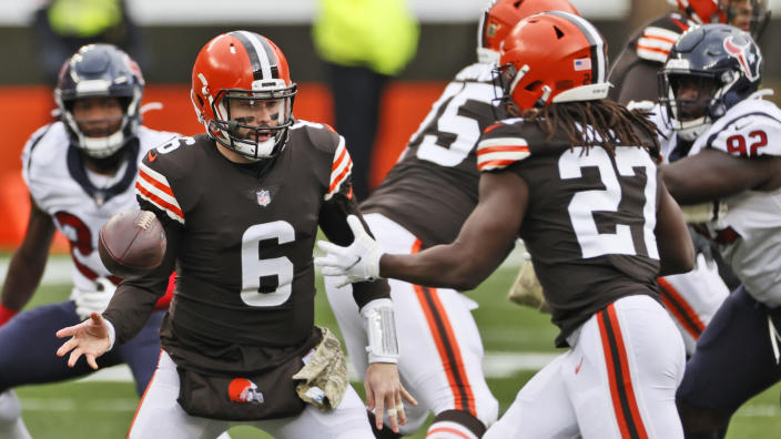 Cleveland Browns quarterback Baker Mayfield (6) tosses the ball to running back Kareem Hunt (27) during the first half of an NFL football game against the Houston Texans, Sunday, Nov. 15, 2020, in Cleveland. (AP Photo/Ron Schwane)