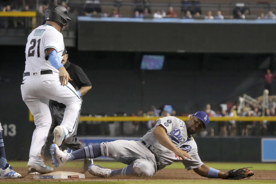 Arizona Diamondbacks' Stephen Vogt (21) hits a single by beating Los Angeles Dodgers first baseman Albert Pujols, right, to the base in the eighth inning during a baseball game, Sunday, June 20, 2021, in Phoenix. (AP Photo/Rick Scuteri)
