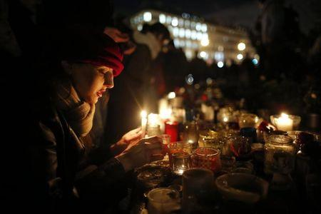 FILE PHOTO: A woman lights a candle as people gather on the Place de la Republique square to pay tribute to the victims of last year's shooting at the French satirical newspaper Charlie Hebdo, in Paris, France, January 7, 2016.  REUTERS/Stephane Mahe