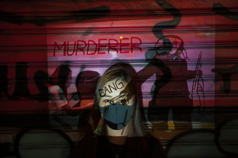 A 24-year-old protester who identified herself as Kathy, poses for a portrait as a projector displays a photograph, previously taken during the unrest, over her at a protest in Hong Kong. Police have arrested thousands of protesters since June, on charges such as illegal assembly and rioting. An attempt last month to impose a city-wide mask ban only further inflamed the demonstrators, who now cover up in defiance. (Photo: Felipe Dana/AP)