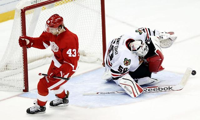 Detroit Red Wings center Darren Helm (43) celebrates scoring a goal against Chicago Blackhawks goalie Corey Crawford (50) in a shootout during an NHL hockey game Wednesday, Jan. 22, 2014, in Detroit. Detroit won 5-4. (AP Photo/Paul Sancya)