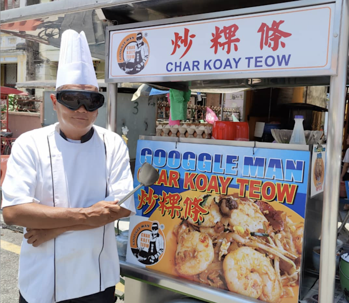 """Singapore's Chef Ah Guan – also known as """"Googgle Man"""" –must wear goggles while cooking to protect his eyes from the intense heat."""