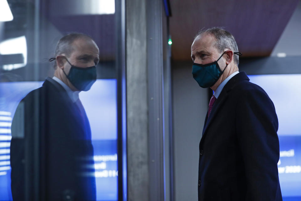Ireland's Prime Minister Micheal Martin leaves at the end of an EU summit in Brussels, Friday, Dec. 11, 2020. European Union leaders have reached a hard-fought deal to cut the bloc's greenhouse gas emissions by at least 55 percent by the end of the decade compared with 1990 levels, avoiding a hugely embarrassing deadlock ahead of a U.N. climate meeting this weekend. (AP Photo/Francisco Seco, Pool)