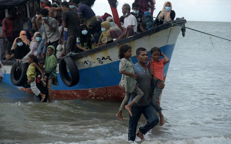 Residents conduct a forced evacuation of Rohingya from ships on the coast of Lancok - Rahmat Mirza/Opn Images/Barcroft Media via Getty Images