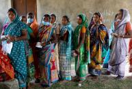 Women wait in line to cast their vote at a polling station in Purulia