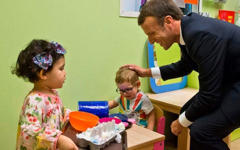 French President Emmanuel Macron (R) visits a nursery school, in Gennevilliers, north of Paris, on October 17, 2017, as part of his action to combat child and youth poverty. - Credit:  MICHEL EULER/AFP