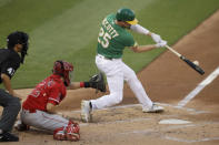 Oakland Athletics' Stephen Piscotty (25) swings for a two run double off Los Angeles Angels pitcher Andrew Heaney in the first inning of a baseball game Friday, Aug. 21, 2020, in Oakland, Calif. (AP Photo/Ben Margot)