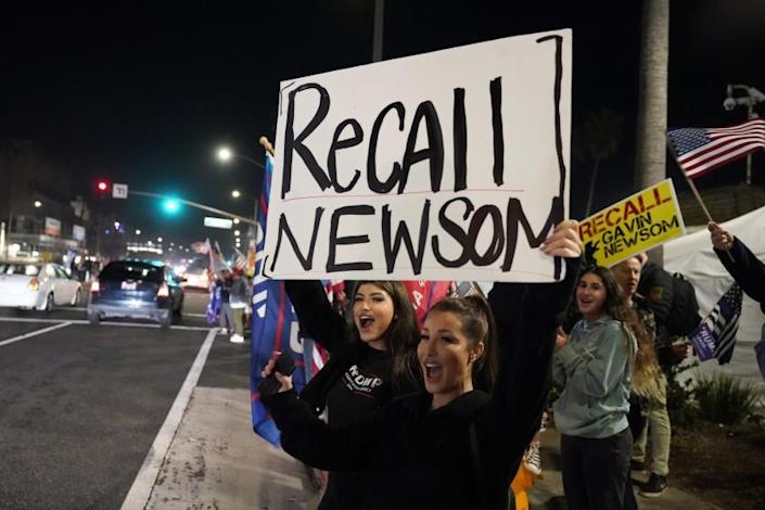 FILE - In this Nov. 21, 2020, file photo, demonstrators shout slogans while carrying a sign calling for a recall on Gov. Gavin Newsom during a protest against a stay-at-home order amid the COVID-19 pandemic in Huntington Beach, Calif. Gov. Newsom is facing a possible recall election as the nation's most populous state struggles to emerge from the coronavirus crisis. Organizers say they have collected more than half of the nearly 1.5 million petition signatures needed to place the recall on the ballot. (AP Photo/Marcio Jose Sanchez, File)