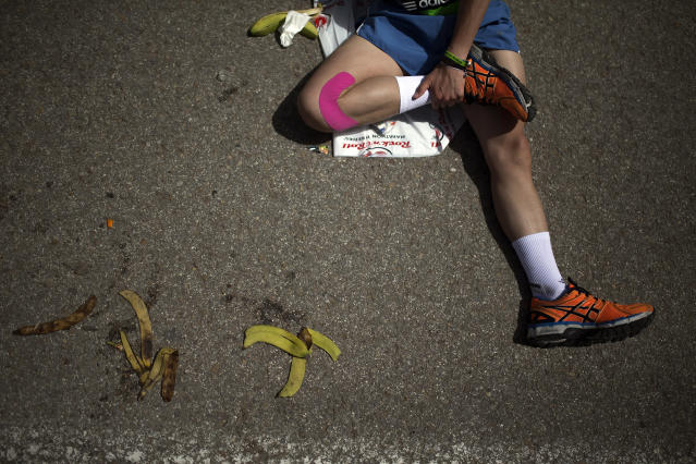 <p>A runner stretches after crossing the finish line in the 37th Madrid Marathon, April 27, 2014. (AP Photo/Andres Kudacki) </p>