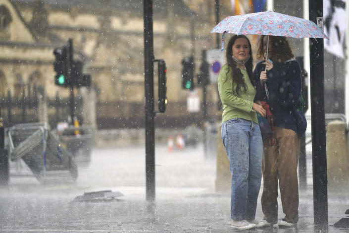 Two women shelter under an umbrella in Parliament Square in central London, Sunday July 25, 2021. Thunderstorms bringing lightning and torrential rain to the south are set to continue until Monday it is forecast. (Victoria Jones/PA via AP)