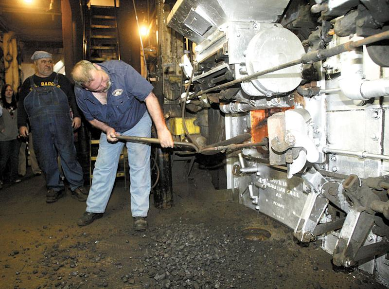 FILE - In this April 28, 2008 file photo S.S. Badger Chief Engineer Chuck Cart shovels coal into the one of the steamship's four boilers in Ludington, Mich. On one level, it's a straightforward case of a business seeking a government permit to discharge wastewater. But when the Environmental Protection Agency rules shortly on whether to let the S.S. Badger car ferry continue dumping ash into Lake Michigan, it will be a milestone in a decades-old effort to keep afloat the last coal-fired steamship operating on U.S. waters. (AP Photo/Jeff Kiessel/Ludington Daily News, File)