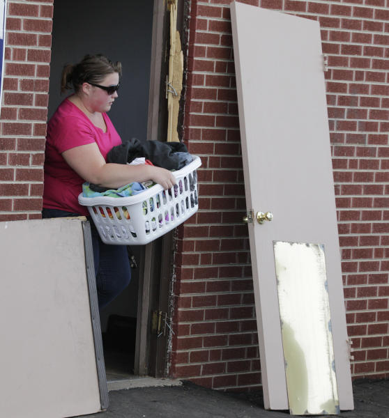 Walking past a door still out of its frame due to police activity, an unidentified resident of the apartment building where suspected Aurora movie theater gunman James Holmes lived, carries a basket to her car, Wednesday, July 25, 2012, after residents were allowed back in the building, which had been closed off by police due to the continuing investigation of the shooting.(AP Photo/Ted S. Warren)