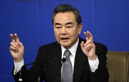 Chinese Foreign Minister Wang gestures as he speaks at a news conference at the annual session of the NPC in Beijing