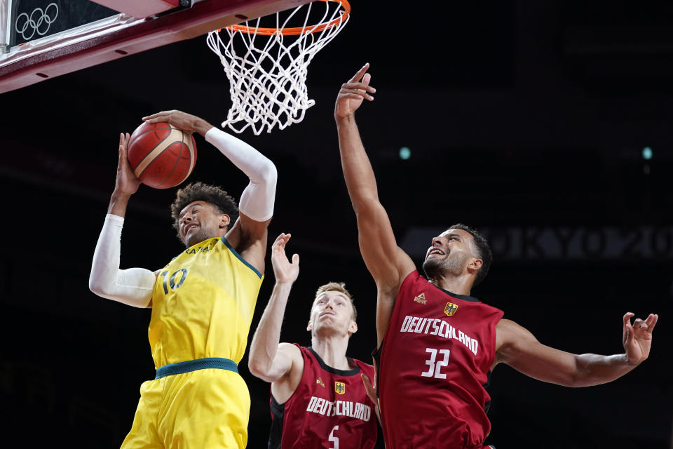 Australia's Matisse Thybulle (10) grabs a rebound in front of Germany's Johannes Thiemann (32) during a men's basketball preliminary round game at the 2020 Summer Olympics, Saturday, July 31, 2021, in Saitama, Japan. (AP Photo/Charlie Neibergall)