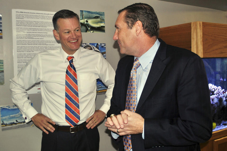 FILE - In this Nov. 27, 2017, file photo, University of Florida athletic director Scott Stricklin, left, smiles as he talks to Florida's new NCAA college football coach Dan Mullen after Mullen arrived at the airport in Gainesville, Fla. Florida's athletic department had a $54.5 million shortfall during the 2020-21 fiscal year because of the coronavirus pandemic, significant financial losses the Gators were able to weather with a supplement from the Southeastern Conference and a sizeable reserve. (AP Photo/Mark Long, File)