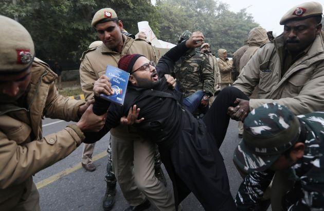 Police officers detain a protesting against the new citizenship law outside Uttar Pradesh Bhawan on Friday, Dec. 27, 2019.