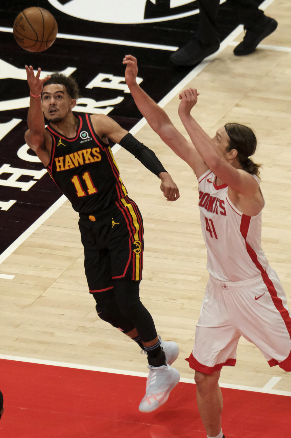 Atlanta Hawks guard Trae Young (11) shoots as Houston Rockets forward Kelly Olynyk (41) rushes in to try to block during the first half of an NBA basketball game on Sunday, May 16, 2021, in Atlanta. (AP Photo/Ben Gray)