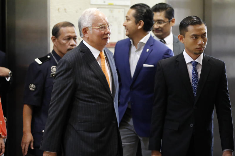 Former Malaysian Prime Minister Najib Razak, left in foreground, arrives at Kuala Lumpur High Court in Kuala Lumpur, Monday, Nov. 11, 2019. An important court ruling Monday in the first corruption trial of Najib will be a test of the legal system and of the credibility of the prime minister who brought about his shocking ouster from office last year. (AP Photo/Vincent Thian)