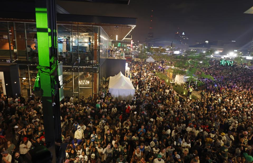 Fans cheer as the Milwaukee Bucks defeated the Phoenix Suns in Game 6 of the NBA basketball finals to win the championship, Tuesday, July 20, 2021, in Milwaukee. (AP Photo/Jeffrey Phelps)