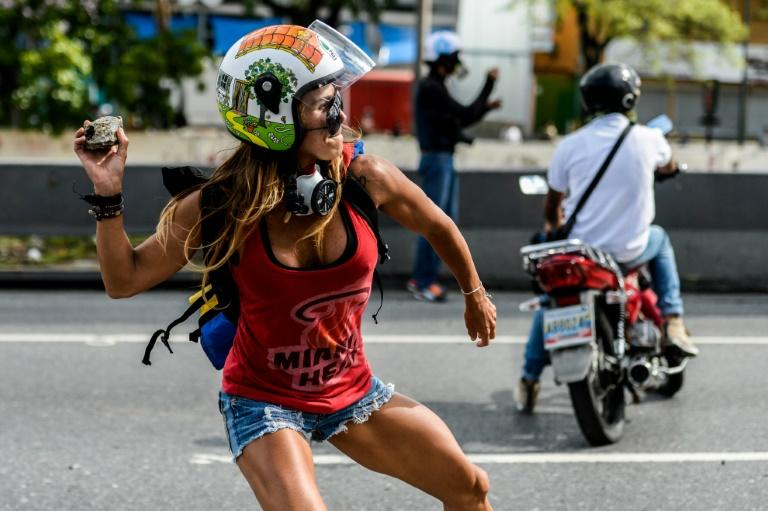 An opposition activist clashes with the police during a march against Venezuelan President Nicolas Maduro
