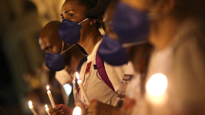 Black movement activists hold candles as they protest against racism and police violence in Rio de Janeiro
