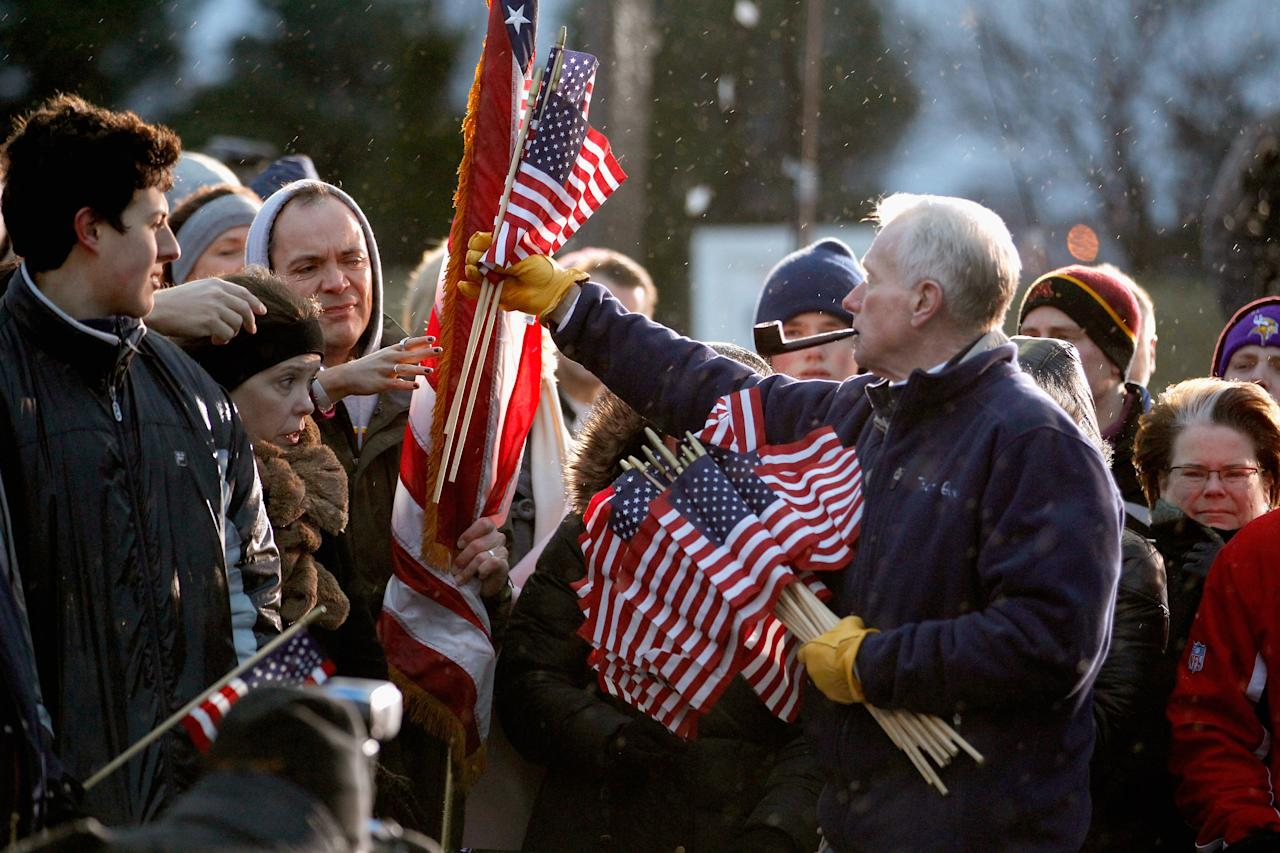 """As a light and steady rain falls, Jim Wilson of Buckingham, Virginia, hand out United States flags to supporters before the start of a campaign rally with former Massachusetts Governor and Republican presidential candidate Mitt Romney at a Hy Vee supermarket December 30, 2011 in West Des Moines, Iowa. Despite cold wind and rain, hundreds of Romney supporters came out to see the candidate just days before the """"first in the nation"""" Iowa Caucuses.  (Photo by Chip Somodevilla/Getty Images)"""