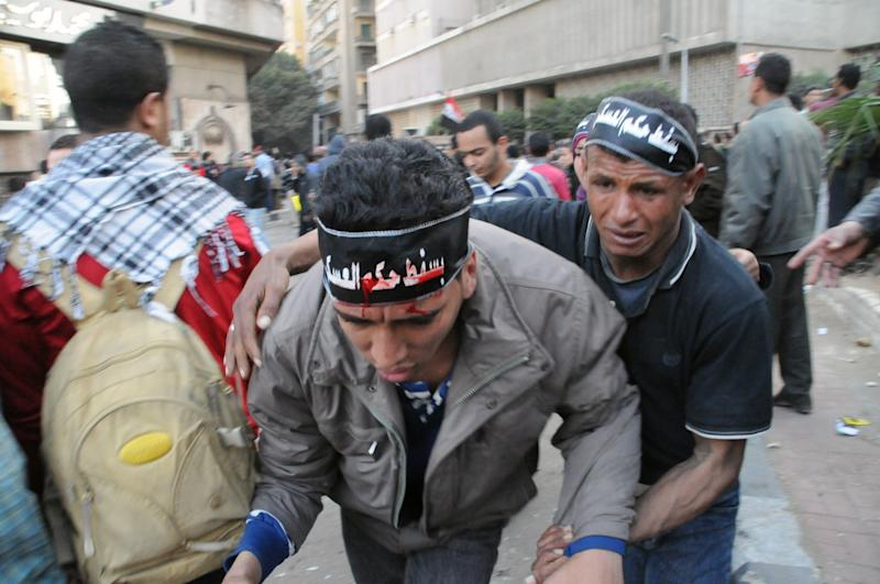 """An injured Egyptian protester is helped by another during clashes outside the US embassy in Cairo, Egypt, Friday, March 9, 2012. Several hundred protesters gathered Friday outside the U.S. Embassy in Cairo, raising their shoes at a picture of President Barack Obama and calling on Egypt to expel Washington's ambassador amid a heated national debate about the trial of Americans working with pro-democracy groups who have been charged with using foreign funding to foment unrest. The protesters headbands, in Arabic, read, """"down with the military rule.""""(AP Photo)"""
