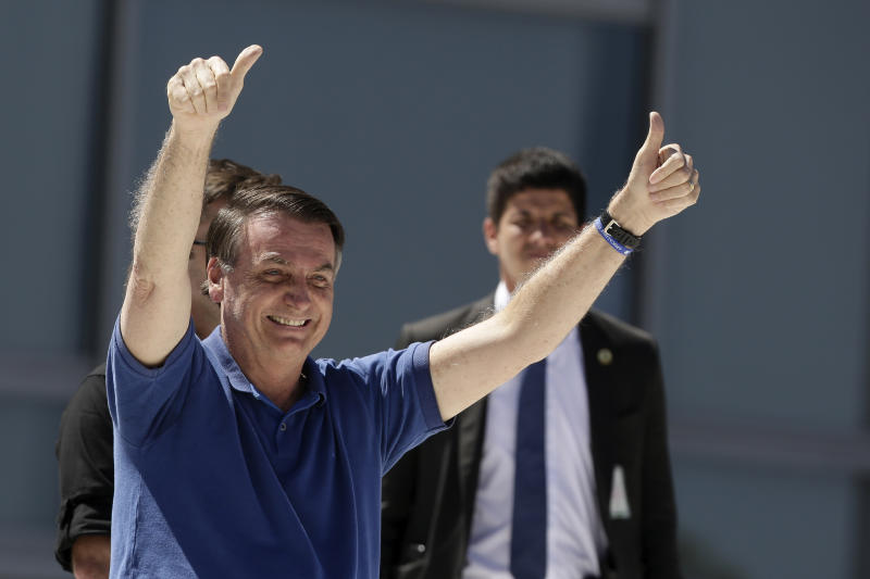 Brazil's President Jair Bolsonaro signals thumbs up to his supporters during a protest against his former Minister of Justice Sergio Moro and the Supreme Court, in front of the Planalto presidential palace, in Brasilia, Brazil, Sunday, May 3, 2020. (AP Photo/Eraldo Peres)