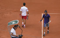 Serbia's Novak Djokovic, top left passes Italy's Lorenzo Musetti as they change ends in a tie break for the second set during their fourth round match on day 9, of the French Open tennis tournament at Roland Garros in Paris, France, Monday, June 7, 2021. (AP Photo/Michel Euler)