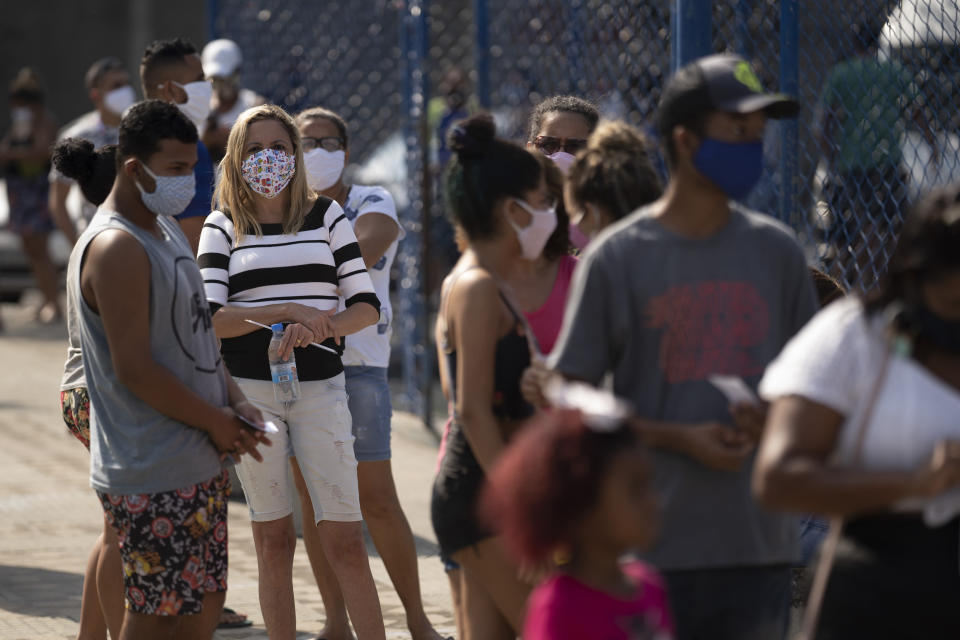 People wait in line for a COVID-19 test amid the new coronavirus pandemic at a plaza in Duque de Caxias, Brazil, Monday, June 8, 2020. Brazil's government has stopped publishing a running total of coronavirus deaths and infections in an extraordinary move that critics call an attempt to hide the true toll of the disease in Latin America's largest nation. (AP Photo/Leo Correa)