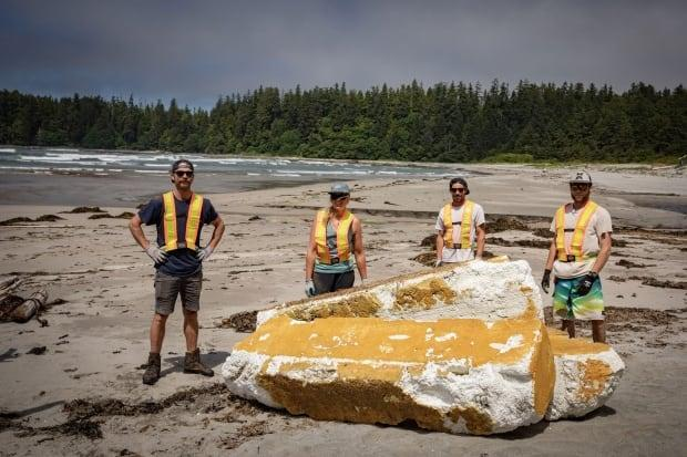 From left to right, cleanup workers Craig Gentry, Emelie Stenberg, Owen Gardiner and Ben Boulton stand in front of giant pieces of styrofoam on a beach near Tofino, B.C. (Greg Rasmussen/CBC - image credit)