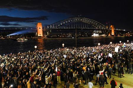 Torchlight protest at racing ad on Sydney Opera House