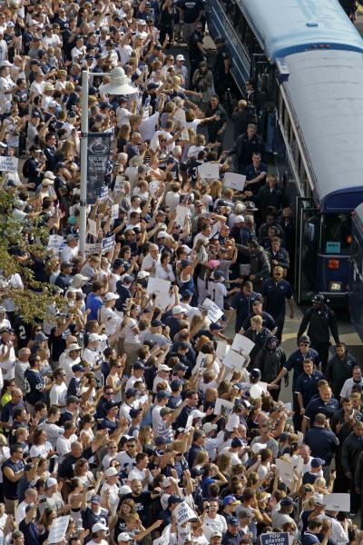 Penn State football fans cheer for the Penn State football team as they arrives by bus at Beaver Stadium for their season opener against Ohio in State College, Pa., Saturday, Sept. 1, 2012. Penn State fans ushered in a new era in the football program with a raucous ovation as the team stormed the field for their first game under coach Bill O'Brien. (AP Photo/Gene J. Puskar)
