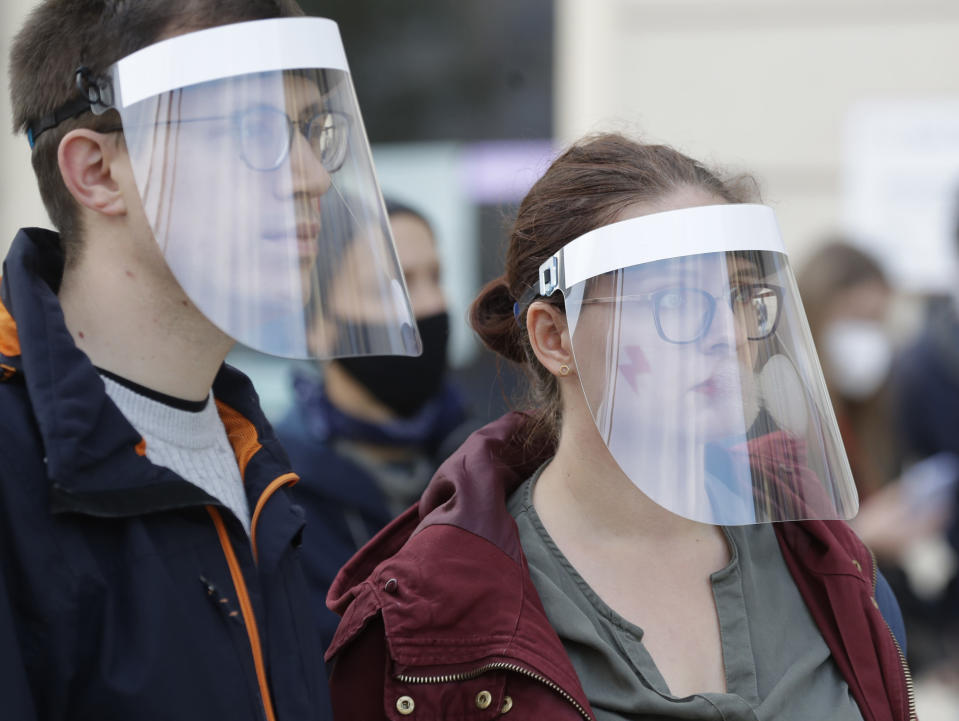 Demonstrators wear protective face masks during a protest a church where they were protesting church support for tightening Poland's already restrictive abortion law in Warsaw, Poland, Sunday, Oct. 25, 2020. Poland constitutional court issued a ruling on Thursday that further restricts abortion rights in Poland, triggering four straight days of protests across Poland.(AP Photo/Czarek Sokolowski)