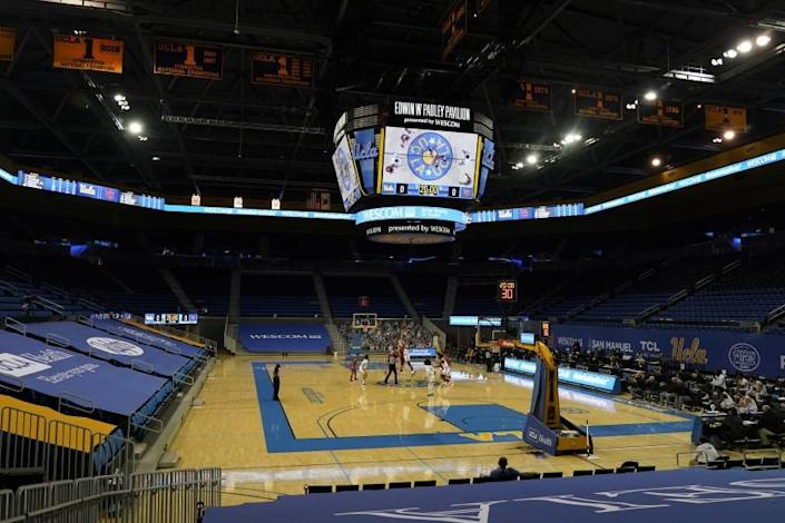 Utah tips off against UCLA at an empty Pauley Pavilion amid the coronavirus pandemic, in an NCAA college basketball game Thursday, Dec. 31, 2020, in Los Angeles. (AP Photo/Marcio Jose Sanchez)
