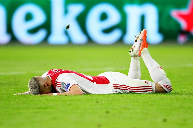 Ziyech is left deflated in the turf as the referee blows for full-time.