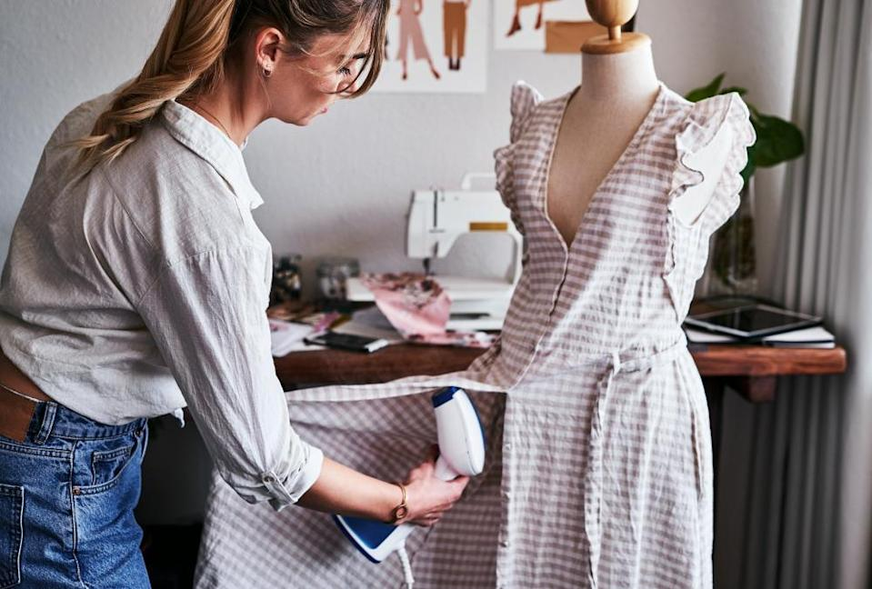 A woman steams a dress on a mannequin.