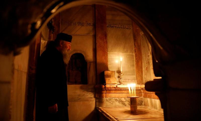 A Greek Orthodox priest stands inside the newly restored Edicule, the ancient structure which according to Christian belief is where Jesus's body was anointed and buried.