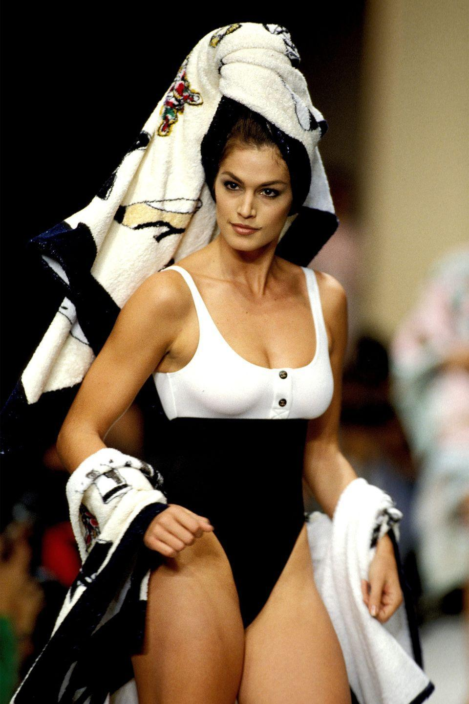 """<p>Before Crawford graced the runway and the covers of all major fashion magazines, she was a girl living in the small town of DeKalb, Illinois. She <a href=""""https://www.vanityfair.com/hollywood/2015/12/cindy-crawford-first-modeling-photo"""" rel=""""nofollow noopener"""" target=""""_blank"""" data-ylk=""""slk:recounted"""" class=""""link rapid-noclick-resp"""">recounted</a> how a poolside photo that a local photographer took of her piqued her interest in modeling. From there, she traveled to Chicago and signed with the modeling agency Elite.</p>"""