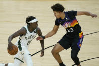 Milwaukee Bucks guard Jrue Holiday (21) drives against Phoenix Suns forward Cameron Johnson (23) during the first half of Game 5 of basketball's NBA Finals, Saturday, July 17, 2021, in Phoenix. (AP Photo/Ross D. Franklin)