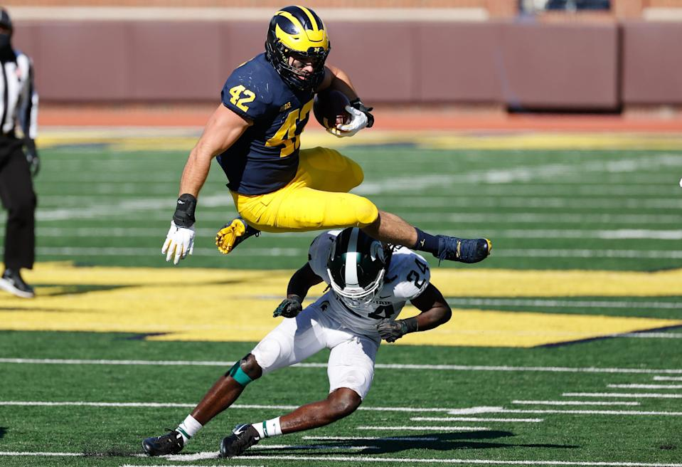 Michigan tight end Ben Mason leaps over Michigan State safety Tre Person in the first half at Michigan Stadium.