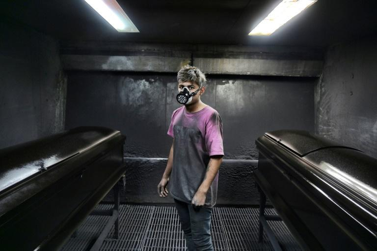 A worker takes a break at a factory making steel coffins in Ecatepec, a suburb next to Mexico City