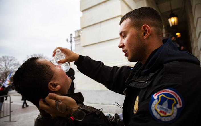 A pro-Trump protester is aided by police officer after suffering the effects of a chemical agent, Jan 6, 2021 - Jon Cherry /Getty Images North America