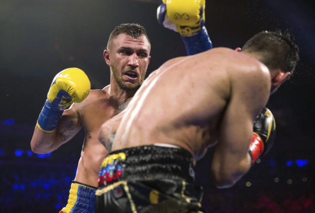 FILE - In this May 12, 2018, file photo, Vasiliy Lomachenko, left, of Ukraine, throws a punch at Jorge Linares, of Venezuela, during the WBA lightweight championship boxing match in New York. Lomachenko is a significant favorite when he defends his two lightweight titles on Friday, April 12, against Britains Anthony Crolla at Staples Center in Los Angeles. (AP Photo/Kevin Hagen, File)