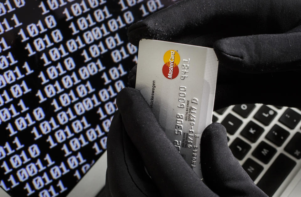 BERLIN, GERMANY - OCTOBER 22: Symbolic feature with topic online crime, data theft and credit card fraudsters, here a close-up of a keyboard of a laptop with hands in black gloves holding a credit card, on October 22, 2013 in Berlin, Germany. (Photo by Thomas Imo/Photothek via Getty Images)