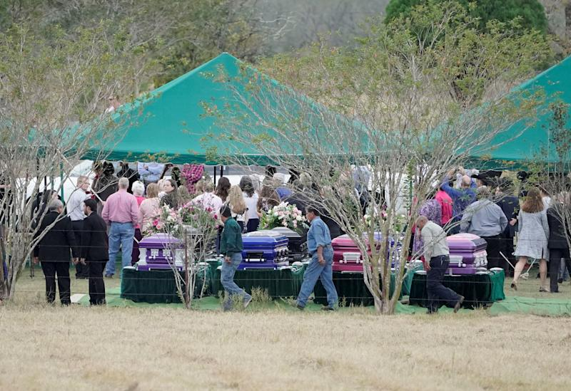 Mourners walk past caskets containing the bodies of members of the Holcombe and Hill families, victims of the Sutherland Springs Baptist church shooting, during a graveside service in Sutherland Springs, Texas, on Nov. 15 (Darren Abate / Reuters)